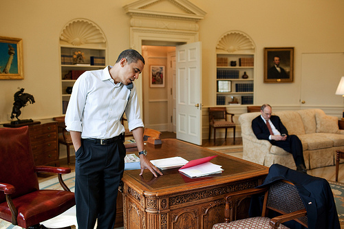 President Barack Obama talks to a Member of Congress on the phone in the Oval Office on Sunday. Assistant to the President for Legislative Affairs Phil Schiliro works in the background. (Official White House Photo by Pete Souza.)